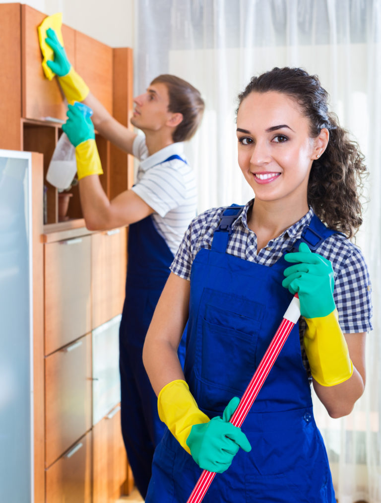 Positive professional cleaners team at the work in ordinary office